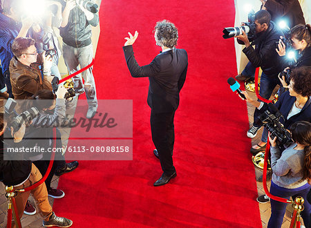 Celebrity arriving at red carpet event and waving at photographing paparazzi Stock Photo - Premium Royalty-Free, Image code: 6113-08088158