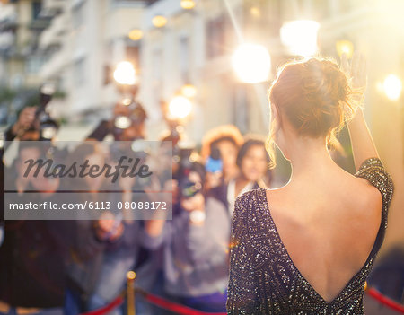 Celebrity waving at paparazzi photographers at event Stock Photo - Premium Royalty-Free, Image code: 6113-08088172