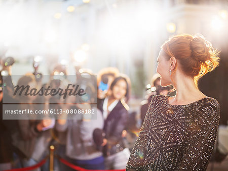 Celebrity turning and smiling at paparazzi photographers at event Stock Photo - Premium Royalty-Free, Image code: 6113-08088182