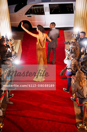 Celebrity couple waving to paparazzi photographers and leaving red carpet event Stock Photo - Premium Royalty-Free, Image code: 6113-08088189