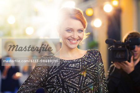 Portrait of smiling celebrity being photographed by paparazzi at event Stock Photo - Premium Royalty-Free, Image code: 6113-08088190
