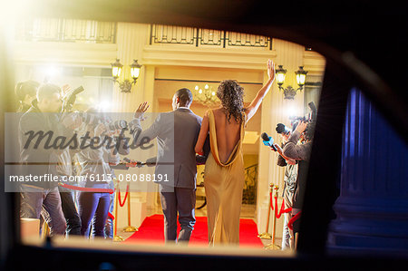 Celebrity couple arriving and waving to paparazzi photographers at red carpet event Stock Photo - Premium Royalty-Free, Image code: 6113-08088191