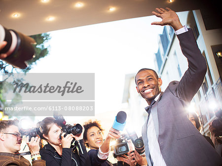 Waving celebrity being interviewed and photographed by paparazzi at event Stock Photo - Premium Royalty-Free, Image code: 6113-08088203