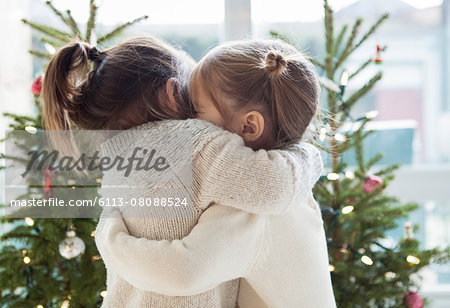 Girls hugging in front of Christmas trees Stock Photo - Premium Royalty-Free, Image code: 6113-08088524