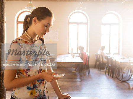 Casual businesswoman with headphones texting with cell phone in sunny office Stock Photo - Premium Royalty-Free, Image code: 6113-08105328