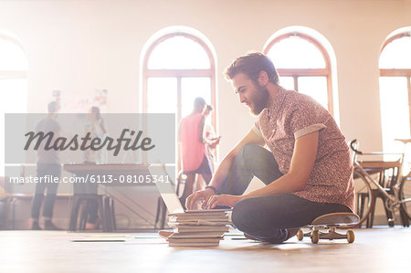 Casual businessman working at laptop from skateboard Stock Photo - Premium Royalty-Free, Image code: 6113-08105341