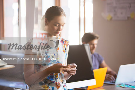 Casual businesswoman with headphones texting on cell phone in office Stock Photo - Premium Royalty-Free, Image code: 6113-08105394