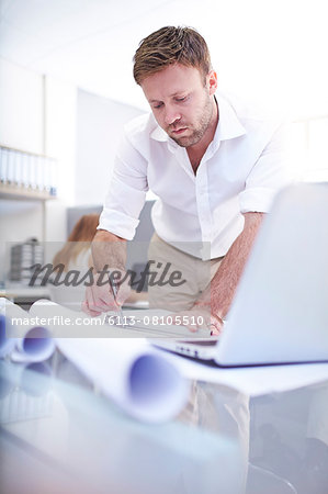 Focused architect drafting blueprint in office Stock Photo - Premium Royalty-Free, Image code: 6113-08105510