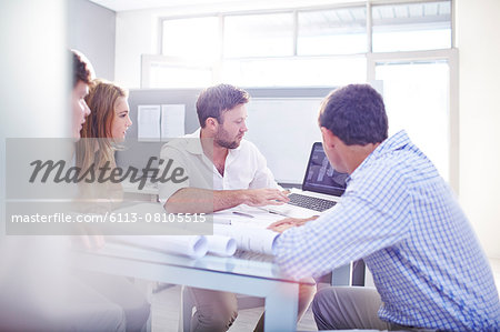 Architects drafting blueprints at laptop in office Stock Photo - Premium Royalty-Free, Image code: 6113-08105515