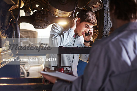 Mechanic and customer talking on cell phone under car Stock Photo - Premium Royalty-Free, Image code: 6113-08184335