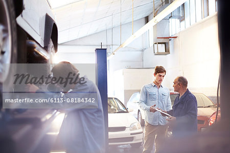 Mechanic speaking with customer in auto repair shop Stock Photo - Premium Royalty-Free, Image code: 6113-08184342