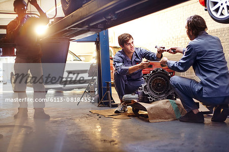 Mechanics discussing part in auto repair shop Stock Photo - Premium Royalty-Free, Image code: 6113-08184352