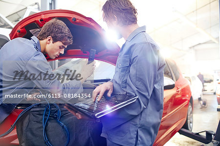 Mechanics with laptop working on car engine in auto repair shop Stock Photo - Premium Royalty-Free, Image code: 6113-08184354