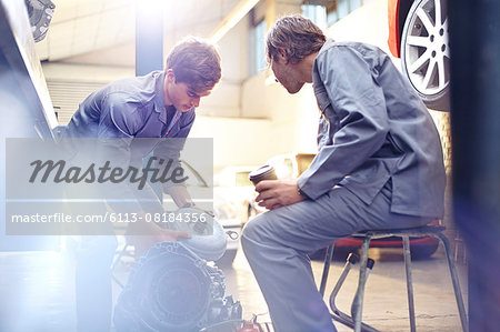 Mechanics examining engine part in auto repair shop Stock Photo - Premium Royalty-Free, Image code: 6113-08184356