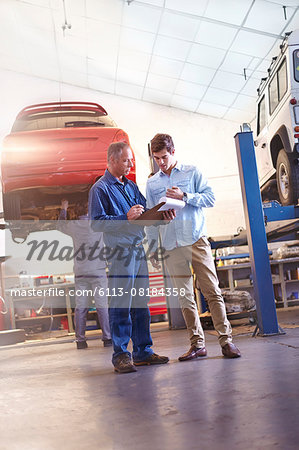 Mechanic with clipboard talking to customer in auto repair shop Stock Photo - Premium Royalty-Free, Image code: 6113-08184358