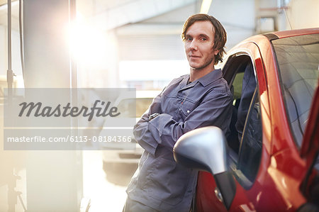 Portrait confident mechanic leaning on car in auto repair shop Stock Photo - Premium Royalty-Free, Image code: 6113-08184366