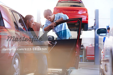 Mechanic with laptop talking to customer at car in auto repair shop Stock Photo - Premium Royalty-Free, Image code: 6113-08184369