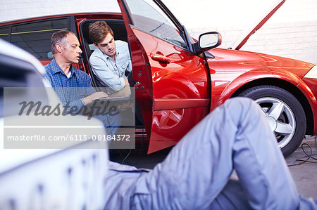 Mechanics with laptop talking at car in auto repair shop Stock Photo - Premium Royalty-Free, Image code: 6113-08184372