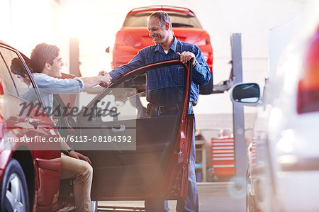 Mechanic and customer in car handshaking in auto repair shop Stock Photo - Premium Royalty-Free, Image code: 6113-08184392
