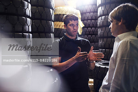 Mechanic and customer talking near stacked tires Stock Photo - Premium Royalty-Free, Image code: 6113-08220186
