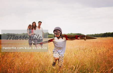 Playful boy with wings in aviator's cap and flying goggles in field Stock Photo - Premium Royalty-Free, Image code: 6113-08220216