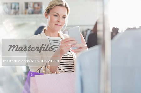 Fashion designer photographing clothing with camera phone Stock Photo - Premium Royalty-Free, Image code: 6113-08220298