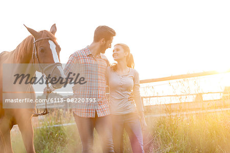 Affectionate couple walking with horse in rural pasture Stock Photo - Premium Royalty-Free, Image code: 6113-08220393