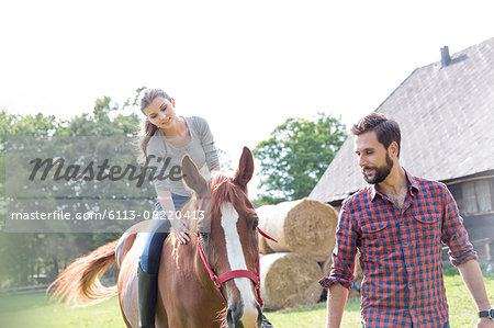 Man leading woman horseback riding in rural pasture Stock Photo - Premium Royalty-Free, Image code: 6113-08220413