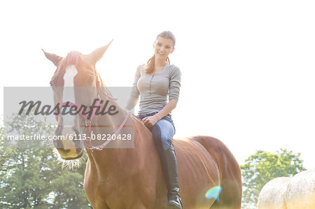 Smiling woman riding horse bareback Stock Photo - Premium Royalty-Free, Image code: 6113-08220428