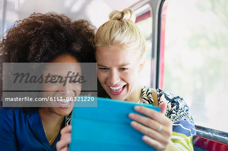 Enthusiastic friends taking selfie with digital tablet on bus Stock Photo - Premium Royalty-Free, Image code: 6113-08321220