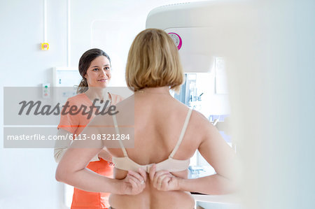 Nurse helping patient prepare for mammogram in examination room Stock Photo - Premium Royalty-Free, Image code: 6113-08321284