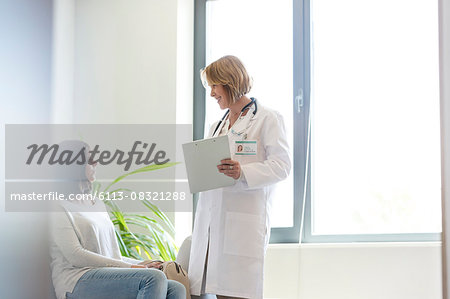 Doctor with medical record talking to patient in waiting room Stock Photo - Premium Royalty-Free, Image code: 6113-08321288