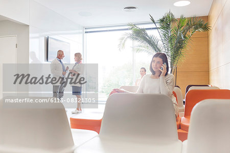 Woman talking on cell phone in hospital lobby Stock Photo - Premium Royalty-Free, Image code: 6113-08321305