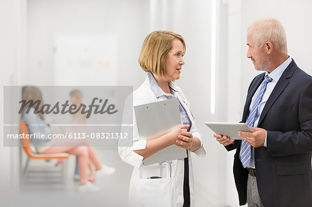 Doctor and administrator with digital tablet talking in hospital corridor Stock Photo - Premium Royalty-Free, Image code: 6113-08321312