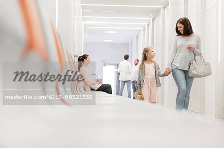 Mother and daughter holding hands walking in hospital corridor Stock Photo - Premium Royalty-Free, Image code: 6113-08321336