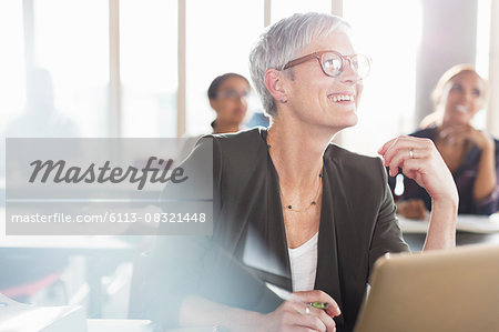 Smiling senior woman at laptop in adult education classroom Stock Photo - Premium Royalty-Free, Image code: 6113-08321448