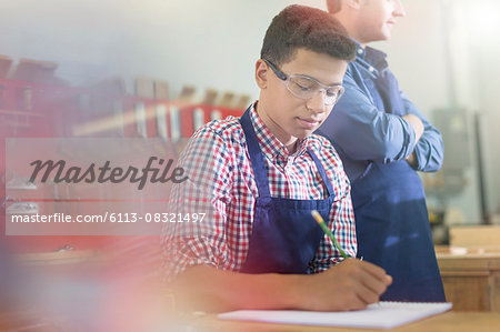 Carpentry student taking notes in workshop Stock Photo - Premium Royalty-Free, Image code: 6113-08321497