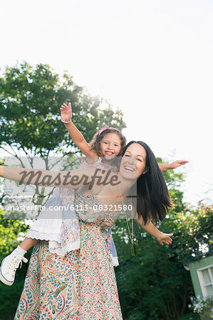 Portrait carefree mother piggybacking daughter with arms outstretched Stock Photo - Premium Royalty-Free, Image code: 6113-08321580