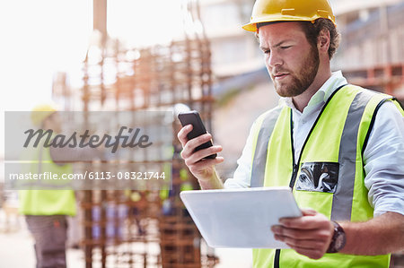 Construction worker with digital tablet texting with cell phone at construction site Stock Photo - Premium Royalty-Free, Image code: 6113-08321744