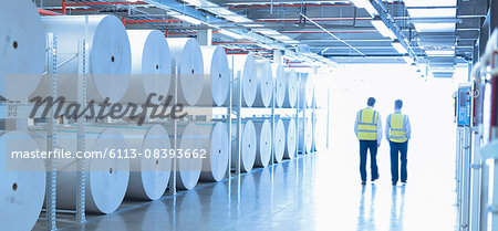 Workers in reflective clothing walking along large paper spools in printing plant Stock Photo - Premium Royalty-Free, Image code: 6113-08393662