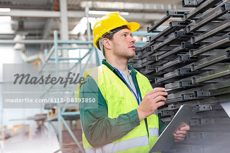 Worker in protective workwear with clipboard examining steel parts in factory Stock Photo - Premium Royalty-Free, Image code: 6113-08393850