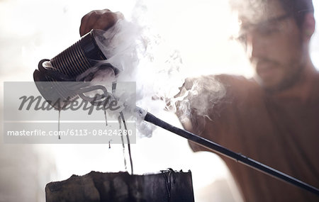 Blacksmith pouring steaming liquid over wrought iron Stock Photo - Premium Royalty-Free, Image code: 6113-08424280