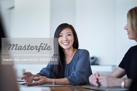 Smiling businesswoman in meeting Stock Photo - Premium Royalty-Free, Image code: 6113-08521403