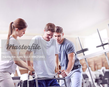 Physical therapists helping man with walker Stock Photo - Premium Royalty-Free, Image code: 6113-08521461