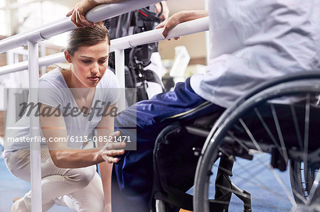 Physical therapist checking man's knee Stock Photo - Premium Royalty-Free, Image code: 6113-08521471