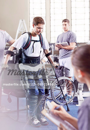 Physical therapists watching man with forearm crutches standing Stock Photo - Premium Royalty-Free, Image code: 6113-08521480