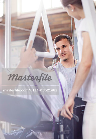 Physical therapists connecting man to equipment Stock Photo - Premium Royalty-Free, Image code: 6113-08521482