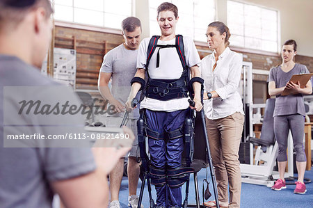 Physical therapists guiding man walking Stock Photo - Premium Royalty-Free, Image code: 6113-08521490