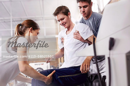 Physical therapists lifting man Stock Photo - Premium Royalty-Free, Image code: 6113-08521501
