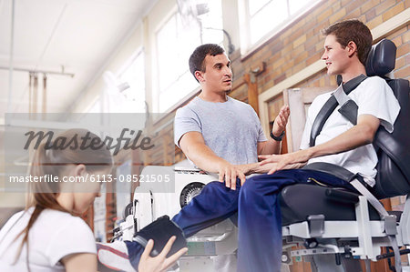 Physical therapist explaining equipment to man Stock Photo - Premium Royalty-Free, Image code: 6113-08521505